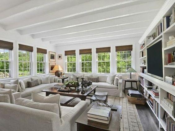 Soggiorno in stile americano con eleganti divani e poltrone in pelle bianca.