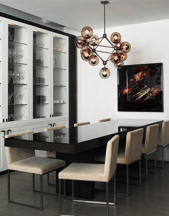 With a sleek table and chairs by Desiron, this SchappacherWhite Architecture designed TriBeCa loft's dining room is topped off with Roll & Hill's Modo 15 Globe Chandelier.