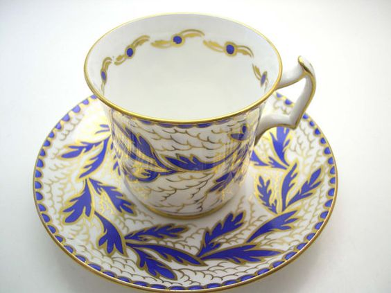 Very nice tea cup and saucer from Royal Chelsea Cobalt blue leaves on white set with gilt decoration. The base and the thumbrest are gilt The backstamp date this cup 1943+ Cup Measures: 2 3/4 high & Saucer Measures 5 5/8 diameter Very good conditon, no chips, no cracks and no gold loss.