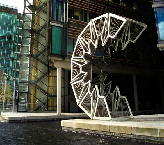 The Rolling Bridge was conceived by British designer Thomas Heatherwick.  The bridge consists of eight triangular sections hinged at the walkway level and connected above by two-part links that can be collapsed towards the deck by hydraulic cylinders. When extended, it resembles a conventional steel and timber footbridge. To allow the passage of boats, the hydraulic pistons are activated and the bridge curls up until its two ends join, to form an octagonal shape.