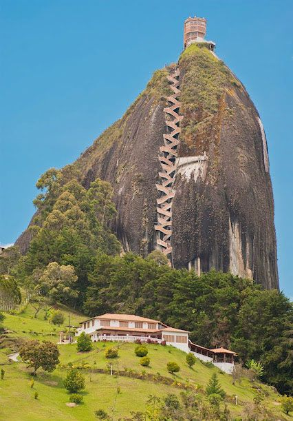 Rock of Guatape, Colombia. Peñónde Guatapé was formed 70 million years ago. Two-thirds of it is below ground. The exposed vertical face is over 200 meters high. Visitors can scale the rock via a staircase built into the side, a climb that includes 649 steps. On the flat top there are food vendors and two gift shops.