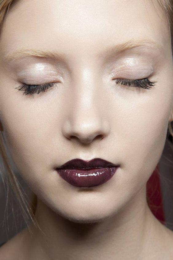 Un maquillage d'hiver avec une ombre à paupières nude et brillante et des lèvres sombres