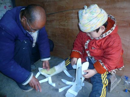 John and his foster grandpa work together to put on his new leg braces in Anhui province.