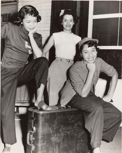 """Photo credit: Charles """"Teenie"""" Harris. Three women, one wearing dark sweater with two daschund appliques, posed around a suitcase in front of brick building c. 1938-1945. Carnegie Museum of Art, Pittsburgh"""