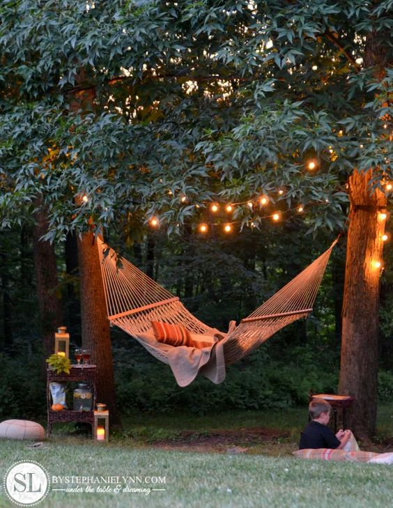Backyard hammock plus tree lights makes magic. Good walk through of what to consider when staging a little backyard nook like this.