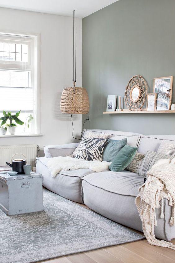 Un mur vert amande enveloppe cet espace salon dans un cocon de douceur