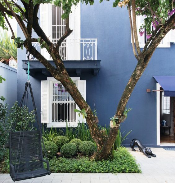 A fachada da casa foi pintada de azul-marinho e exibe piso de ladrilho hidráulico da Dalle Piagge. Paisagismo de Cris Bermudez, balanço da Tidelli e escultura de Eloiza Trindade (Foto: André Klotz / Editora Globo)