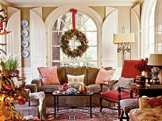 Wreath hung over a large arched window with red ribbon