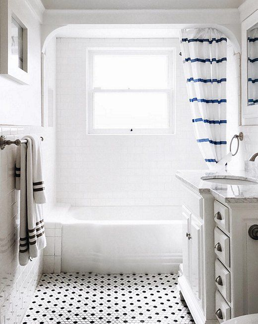 This classic black and white bath gets a modern dose of color from a fun striped shower curtain.