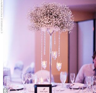 Silver candlesticks topped with baby's breath and hanging candles gave the tables a wintry vibe.