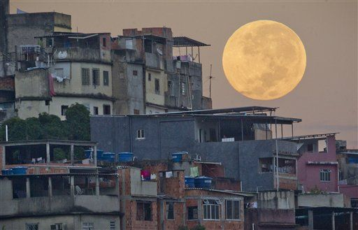 """The """"supermoon"""" appears behind the Mare shanty town complex in Rio de Janeiro. (Photo: AP/Victor R. Caivano"""