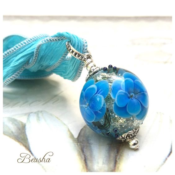 Single bead necklace with lots of silver glitter inside and flowers in aquamarine https://www.etsy.com/de/listing/263081420/glittery-handmade-lampwork-single-bead