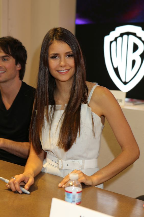 THE VAMPIRE DIARIES star Nina Dobrev pauses for a pic at the Warner Bros. booth at Comic-Con 2012; co-star Ian Somerhalder sits to her left (© WBEI. All Rights Reserved.)