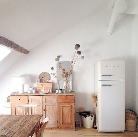 Vintage style decor in a kitchen with a frm table, Smeg frig, and antique sideboard. Lucille Gauthier-Braud's kitchen in Paris. #modernfarmhouse #Smeg #kitchen