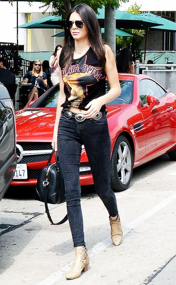 Kendall Jenner wears a Givenchy t-shirt, belted skinny jeans, snakeskin boots, a Givenchy duffle bag, and aviator sunglasses