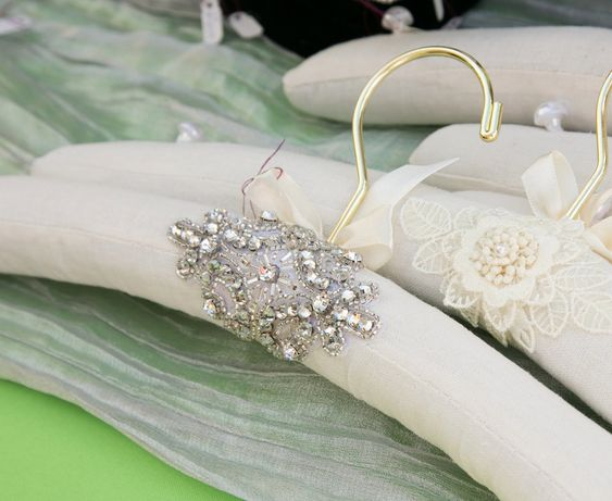 "Best selling wedding gown hanger:  this heavy duty ivory padded hanger is  embellished with a quality Swarovski rhinestone applique - a lasting  keepsake gift for your wedding day...a great gift for your bridesmaids..  Hanger is 17"" long covered with ivory fabric, fully padded with batting -  not foam - has white buttons on each end for your dress straps and a gold  hook.  Carefully packaged and shipped via USPS mail with insurance and tracking."