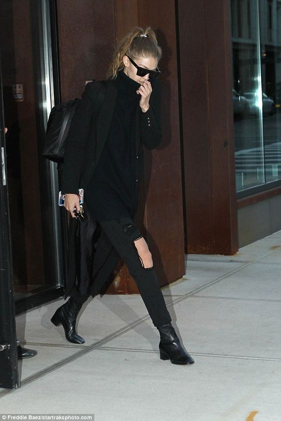 Hiding: The supermodel wore all black and pulled her coat to cover half her face...: