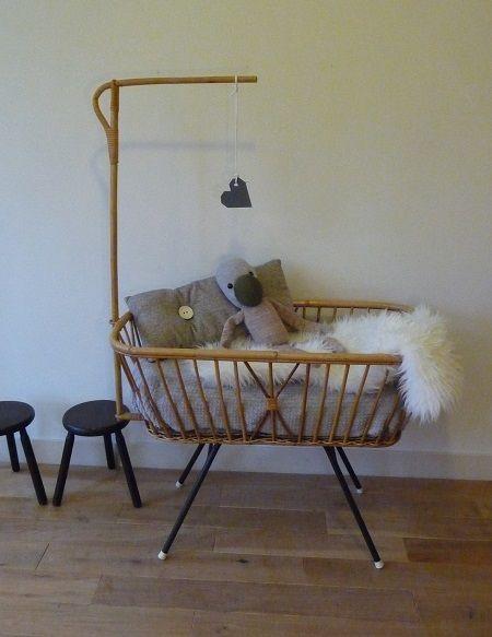 50's rattan crib, cradle.  Rotan Rohé wieg uit de jaren '50.  Eenvoudige wieg met schuimrubberen matrasje. Rotan frame, houten bedbodem en donkerbruine ijzeren onderstel met witte vloerdoppen. Het hemeltje is makkelijk los te halen.  Afmetingen: l 95 x b 54 x h 72 cm.