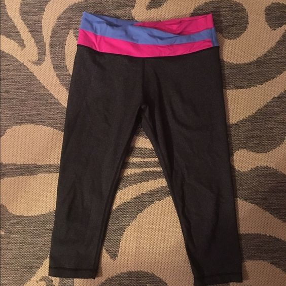 Cropped Grey lulu lemon pants with pink/blue band Cropped gray pants with an overlapped pink and blue band, worn a few times, in good condition, has a pocket in the back of the band Lulu lemon Pants Leggings