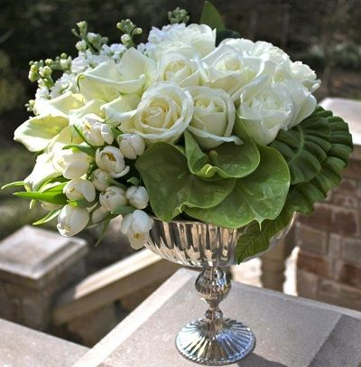 White roses, tulips, mini calla lillies and stock with green anthurium in a silver chalice
