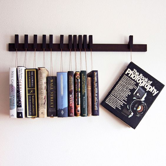 This awesome book rack suspends and displays up to 12 books with ingenious pins that hold each tome in place using small wood plates hung on beige waxed cotton. On sale on fab.com
