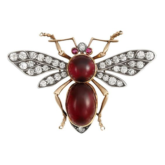 Antique Silver, Gold, Cabochon Garnet and Diamond Insect Brooch  Centering one round cabochon garnet approximately 8.2 mm., and one oval cabochon garnet approximately 14.0 x 9.0 x 5.6 mm., tipped by 2 old European-cut diamonds, with small round cabochon ruby eyes, flanked by wings set with 32 old European-cut diamonds, diamonds altogether approximately 1.35 cts., circa 1870