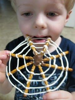 """Pretzel spider webs  - pretzel sticks   - white chocolate/bark candy coating  - chocolate (baker's, candy coating, or chips would probably all work)  - raisins  - baggie or pastry bag  - wax paper     Directions:  Lay out your pretzels on the wax paper in """"starburst"""" arrangements of 6 or 8 pretzels (it's a good idea to put it on a cookie sheet for transport stability)."""