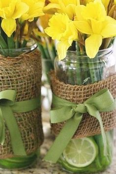 A great idea for country chic wedding centerpieces - daffodils in jars wrapped with burlap and matching ribbon with limes.