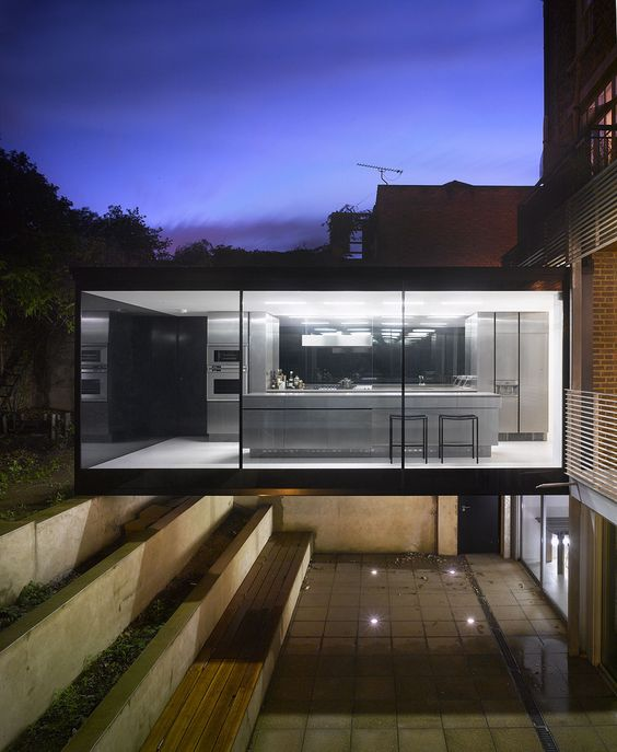 Cross Street, London, by Paul Archer Design. The back wall of the property was removed and the garden excavated to create a two storey elevation of glass, with a bridge structure housing the new kitchen. Stunning.