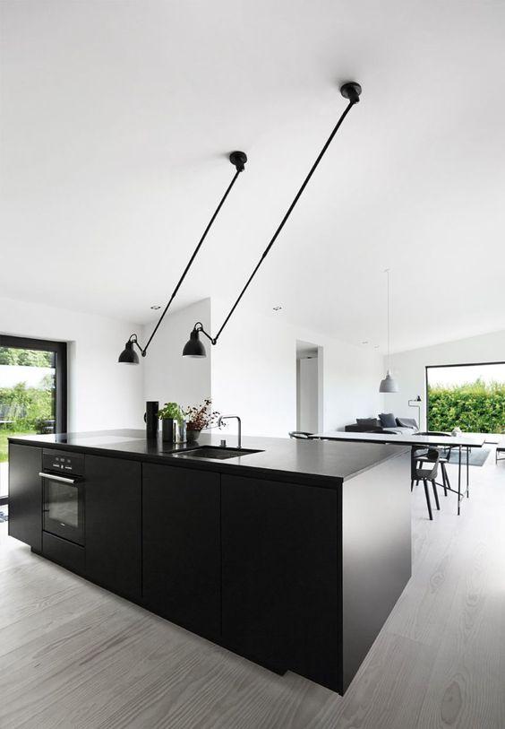 Køkkenet fra kvik består af højskabe i hvidt og køkkenø i sort ...