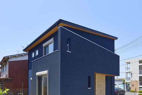ネイビーブルーの外壁で力強く格好良いお家に 玄関の壁のタイル 木目