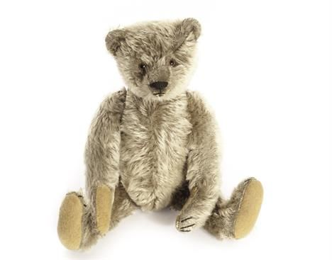 A Steiff brown mohair Teddy Bear, 1920s, faded to a lovely grey colour, clear and black glass eyes with brown backs, pronounced muzzle, black stitched nose, mouth and claws, swivel head, jointed elongated limbs with felt pads, hump, inoperative squeaker and FF button - 11½in. (29.5cm.) high (right foot pad replaced, very slight wear and hand pads with slight restoration)