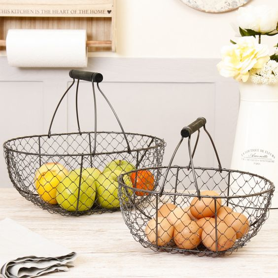 This set of 2 farmhouse chicken wire trugs are a great way to add extra storage capacity to your kitchen. Featuring a black wooden handle these baskets can be used to store eggs or as a rustic style fruit bowl for added country decoration. The smaller basket fits perfectly inside the larger making this set easy to store when not in use.
