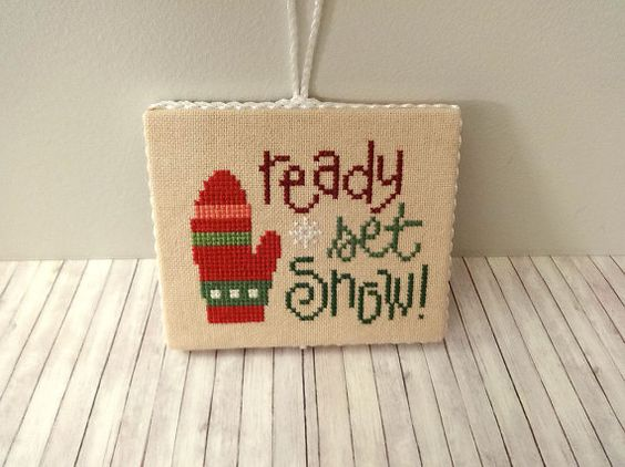 This handmade cross stitch ornament features a whimsical Ready Set Snow design that has been hand-stitched on 28 ct lambswool linen using