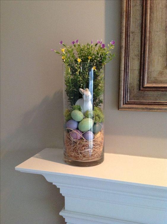 Ideia de decoração para a Páscoa: vaso com palha, ovos coloridos, coelhinho e flores.