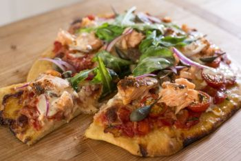 Smoked salmon pizza with tomato, rocket, capers and lemon creme