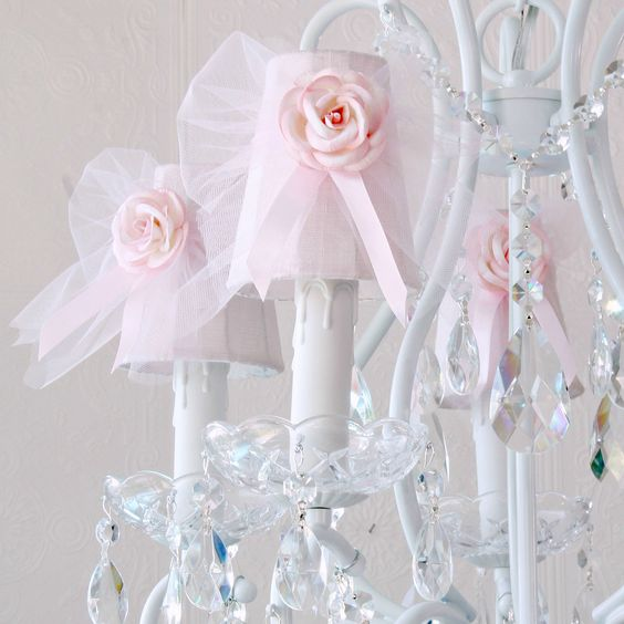 This adorable vintage-inspired 5-light white chandelier has been adorned with gorgeous pink Dupioni Silk shades, decorated with sweet pink tulle bows, satin ribbons and pink roses. Fancy-cut Glass Bobeches, plenty of crystal teardrop prisms, French pendants and layers of crystal chain-swags add loads of glam and sparkle! <BR><BR>Get the complete look with our matching wall sconces, table lamp, Night-light, and picture frames! <BR><BR> • Antique White/Pink<BR> • Dupioni Silk Shades<BR> • ...