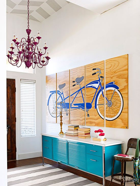 Make way for functions beyond receiving guests, and stay a while for arrangements of fanciful furnishings. In this fetching foyer, a painted steel cabinet provides mudroom-style storage in a chromatic form. A pentaptych comprised of plywood panels provides an over-scale depiction of a way-cool bicycle built for two. The area rug echoes the chevrons painted on the ceiling, while an unexpectedly elegant chandelier classes up the eclectic entry.: