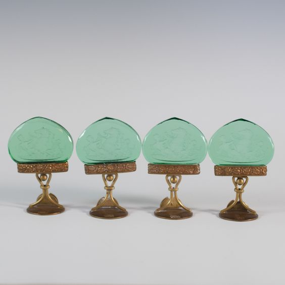 DESCRIPTION: A set of four Austrian antique napkin holders. The silver frame is an elegant curve design with a floral motif on top that holds in place a cut piece of green glass. Etched into the glass is a depiction of a female wrestling with a horse as a boy sits on the back of the horse blowing through a cornucopia horn. The holders on the frame are a little warped but still attached to the base. CIRCA: early 20th century ORIGIN: Austria DIMENSIONS: 2 1/4'' H