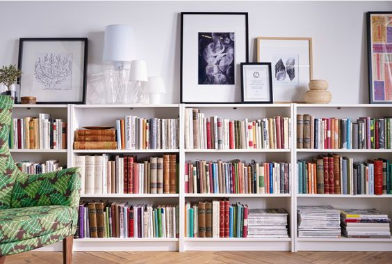 A row of IKEA bookcases lines a wall. On top is framed art and lamps. Billy bookcase: 39.99 http://www.ikea.com/us/en/catalog/categories/departments/living_room/roomset/20151_idst08a/