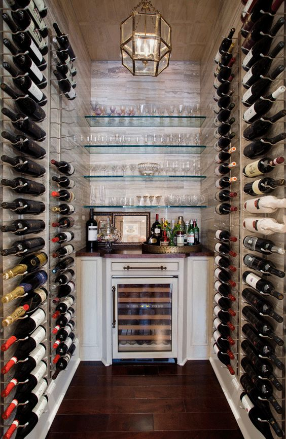 Wine room with bottles well displayed on racks, mounted on walls of crosscut travertine. Wood veneered wallpaper covers the ceiling. #WineCellar