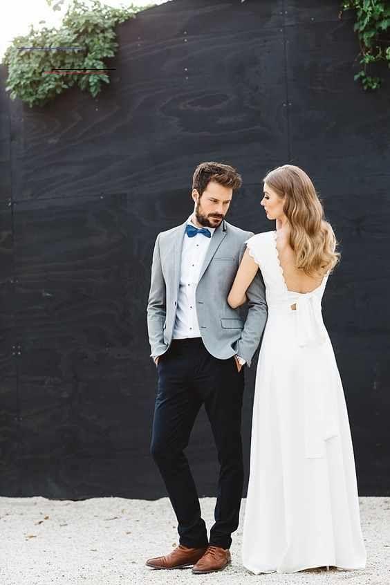 A Grey Blazer A White Shirt A Bold Blue Bow Tie Black Pants