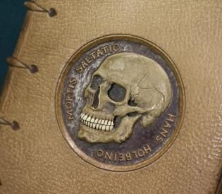 "Cover of a 1813 edition of 'Dance of Death, bound in human skin, with a cover inlay of a toothsome skull carved from human bone.  --------  Boston book fair is skin-sational By Marie Szaniszlo/Boston Herald – November 15, 2009 – -------- If you love old books, you will love the Boston International Antiquarian Book Fair. And if you love the macabre, you will love Hans Holbein's ""Dance of Death.""  The 1813 edition, tucked in a corner of one of the Hynes Convention Center, is bound in human skin a"