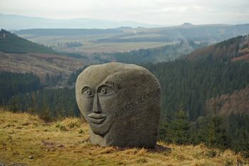 The Talking Head Stane. One of the Seven Stanes. It is made from a 1.5 tonne glacial granite boulder and looks south towards Ae village and the Solway. The stane has a carved mouth, ears and eyes and is inscribed with the translation of a Norwegian poem.