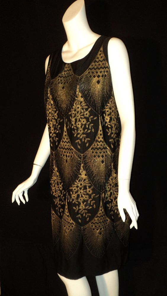 Talk about an amazing dress. Just arrived and here for your viewing. This was deaccessed from the Brooklyn Museum. 1926 embroidered lame party dress. No label. Black silk with an Art Deco pattern of geometric and floral designs. Bust measures 36, dress is 38 hips. Made to be worn loosely. Excellent original condition and a fine authentic period piece of wearable art. Worthy of any antique clothing collection. Perfect for New Years Eve. Feel free to contact me via email