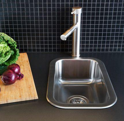 Schmale Spüle in dunkler Arbeitsplatte mit Hackbrett und Gemüse - spüle für küche