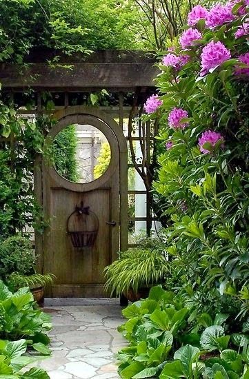Garden Gate Ideas and Beautiful Gardens to Inspire! An arched rustic door with round window leads to a lush garden flowering with blooms. #gardengate #gardenideas #summerstyle #outdoorliving #landscapeideas