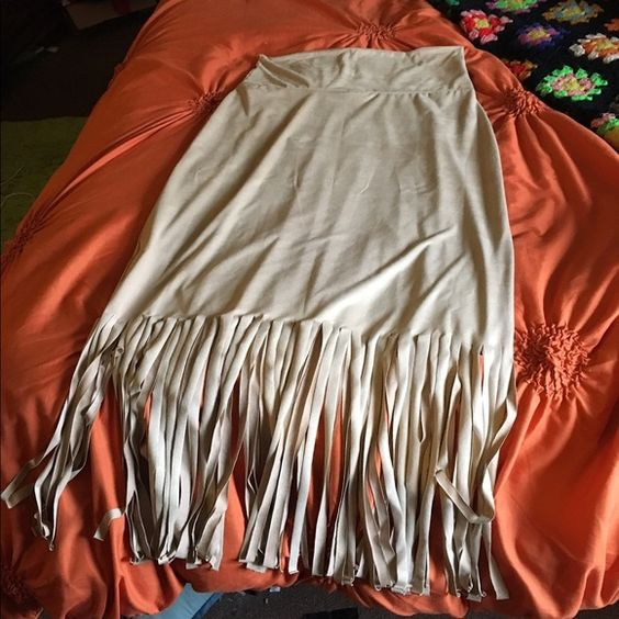 Light tan long skirt with fringe 90% polyester and 10% spandex. The skirt is extremely soft and comfortable. Tags are still on it it's never been worn. Romeo & Juliet Couture Skirts Maxi