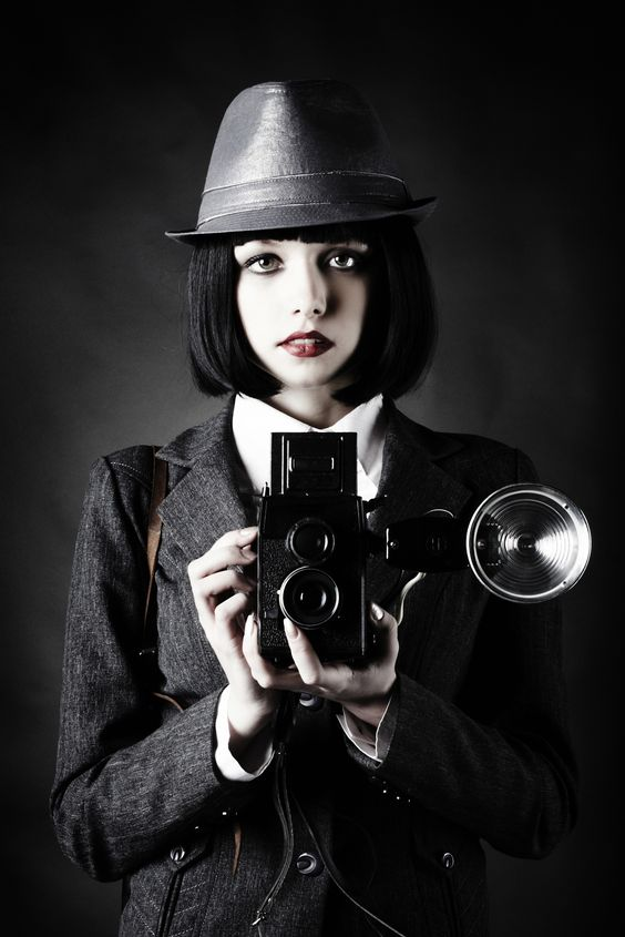 young woman and retro camera - Retro looking young beautiful woman holding a vintage retro camera.
