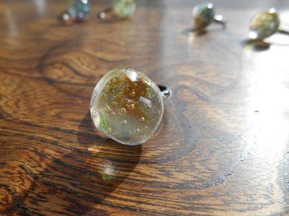 ガラスで作った玉を指輪にしました。透明のガラスに、少し色を足したり気泡を入れて、光に輝く氷のイメージです。冬の森から拾ってきたような氷をひとつぶ、いかがですか... ハンドメイド、手作り、手仕事品の通販・販売・購入ならCreema。